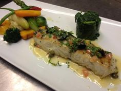 New Zealand Grouper served in Puttenesca Sauce and served with market fresh vegetables and sautéed spinach
