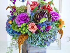 Blue and purple hydrangeas, cabbage roses, an artichoke flower, lilies, and tea roses by Christine Noelle of  Dilly Lily