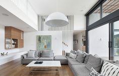 modern family room | oversized sectional | wood | white | oversized pendant | slatted wall | west coast | stepping house | bowen architecture