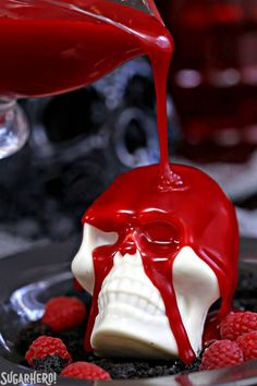 Melting Chocolate Skulls – white chocolate skulls filled with brownies and raspberries. Pour warm, blood-red ganache on top to reveal the goodies inside! | From SugarHero.com