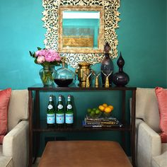 Dalliance Design - living rooms - teal walls, teal living room walls, gold mirror, ornate mirror, gold ornate mirror, ornate gold mirror, wood console table, purple bottles, genie bottles, purple genie bottles, vintage martini set, moroccan ottoman, leather moroccan ottoman, caramel ottoman, caramel leather ottoman, jute rug, chaise lounge, ivory chaise lounge, pink pillows,
