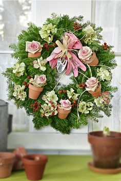 "There's a Wreath for Everyone… | Julie's Floral Lifestyle Blog...cute little flower pots with roses on this gardener's wreat with a spade and glove ""ribbon""..."