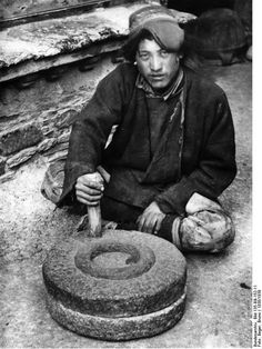 Tibetan with his hand grindstone.From the Nazi's Tibetexpedition.Photographer Beger, Bruno. 1938.