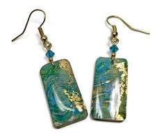 Handmade Polymer clay & Resin Long Dangle Earrings with genuine Swarovski Teal crystals This Exotic Earring Set is handmade & designed by me, in my sunny Florida studio. They are lightweight & easy to wear,made on Gold-tone ear wires, hypoallergenic. I just know you will be thrilled with unique earrings! Size: approx.1 1/2 long rectangle x 3/8 wide dangle length from ear (about 2 1/4)   2016 Beadazzle Me All copyright and reproduction rights are retained by the artist…