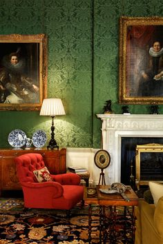 Green damask walls, red tufted chair, blue and white porcelain, rug - interior Design by Alidad