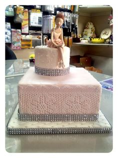Ella's ballerina birthday cake.  2 tiered cake covered in pale pink vanilla fondant.  Base tier accented with white sugar veil to give it the look of lace surrounding the cake.  The bases have been adorned with  silver bling.  The ballerina on top of the cake has been hand sculpted and hand painted.  The cake board is covered in vanilla white fondant which has been quilted and adorned with white sugar beads.