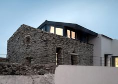 stone ruins combined with modern architecture by OrgAnica Arquitectura in portugal
