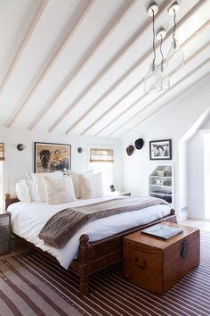 A striped rug and neutral bed linens in a room with a pitched ceiling.