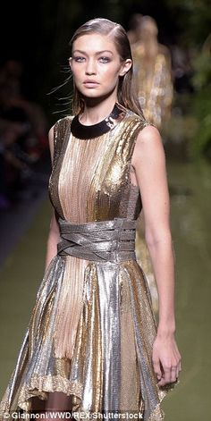 Twice as nice:And that wasn't the only glamorous look to grace the runway as Gigi slipped into a more conservative but still sexy golden gown.Adding to the glamour she wore her golden locks slicked back to expose her decolletage