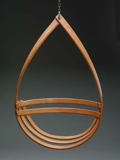 """Walker Weed - A hanging chair, composed of a bentwood slat shaped into a teardrop form, with two curved slats placed horizontally to form the back, to which are joined two additional curved slats forming the seat. The chair is suspended by an iron hook and chain at the top of the""""teardrop."""""""