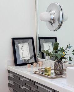 O lavabo tem bancada com detalhes de madeira acinzentada e arandela. O projeto leva a assinatura dos arquitetos Carla Mattioli e Maurício Pinheiro Lima (Foto: Lufe Gomes/ Editora Globo)