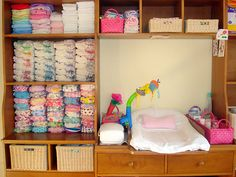 This is a great organization idea. Looks like a television or entertainment center converted to a changing station. And check out the cloth diapers! I just may go that route with the next baby ;)