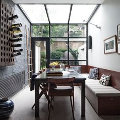 Dining room - The brick wall in this dining area has been painted with graphite-coloured paint for a gritty feel. The long bench, which seats up to 12, houses cushions for use in the garden.
