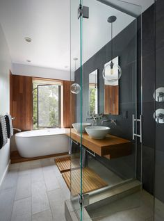 In Brooklyn's Prospect Heights, this townhouse by Etelamaki Architecture has a spa-like bathroom with mixed materials that include a slate wall behind the double sinks, which are suspended on a teak vanity. The freestanding tub sits on a raised wooden bed that continues up the wall behind it.