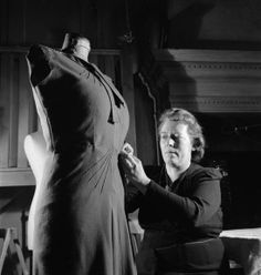 In the workrooms of the fashion designer Norman Hartnell in London, a seamstress fits an afternoon frock onto a stand.