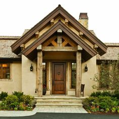 The exterior of this home features earth-toned stucco and natural wood beam construction. Design by http://www.gravitaslc.com/