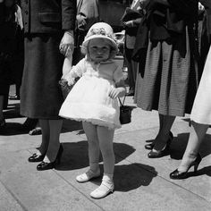 A little girl in her short white dress with hat and black purse standing amongst women's legs. Untitled, Undated