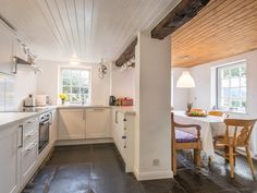 The quirky open plan kitchen and breakfast area with original stone flagged floor and chunky oak beams.
