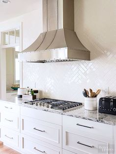 Glossy tiles -- basic subway tile in a herringbone pattern -- cover the entire wall behind the vent hood for a high-impact, low-maintenance backsplash. Drawers below the cooktop simplify food prep by putting pots and pans within easy reach. Kitchen Redo, Kitchen Tiles, New Kitchen, Kitchen Remodel, Kitchen Hoods, Kitchen Cabinets, Herringbone Backsplash, Herringbone Pattern, Herringbone Subway Tile