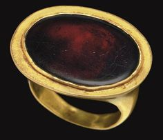 A GREEK GOLD AND GARNET FINGER RING   HELLENISTIC PERIOD, CIRCA 2ND-1ST CENTURY B.C.   The plain hoop flat on the interior, rounded on the exterior, widening towards the large oval bezel, set with a flat oval stone