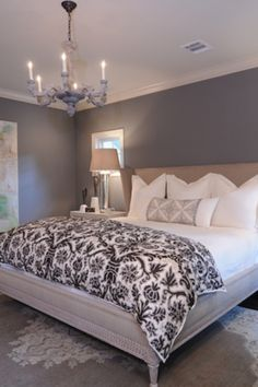 grey paint on the walls. white bedding. clean and simple feel to this bedroom.