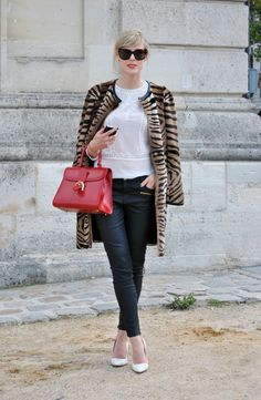 jeans with heels.  Cross your legs when being photographed.  Sunglasses.  Nice bag.  But you can just tell she's American.  How?  1) blonde hair, 2) leopard coat, 3) red purse, 4) white shoes.  A French girl would have dark hair and would layer black on brown on black.  Plus, the smile.  A dead give away.