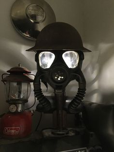 Gas Mask Lamp, made with a Navy gas mask, my great grandfathers helmet, some black pipe and imagination. Alice In Wonderland Room, Pulley Light, Cafe Concept, Man Cave Art, Black Pipe, Steampunk Lamp, Scrap Metal Art, Automotive Decor, Pipe Lamp