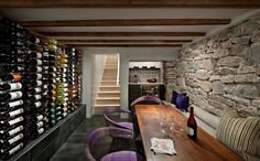 Chairs add color and informal charm to the wine tasting room with stone walls