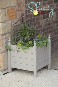 Ana White has added finials (furniture feet) to the top of a pine planter and painted it gray to create a more expensive looking garden planter.