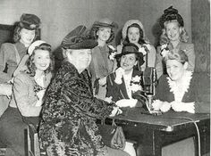 """1946 photo of Eleanor Roosevelt with the Goldwyn Girls during a publicity tour for the movie """"The Kid From Brooklyn"""". B-western actress Virginia Belmont is in the back center, hat on, directly behind Mrs. Roosevelt. The only other ID'd girl is Shirley Ballard at the bottom left. Can anyone ID any of the other ladies? Belmont co-starred in B-westerns with Johnny Mack Brown, Jimmy Wakely, Hopalong Cassidy and in the serial """"Dangers of the Canadian Mounted"""" ('48)."""