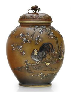 A soft-metal-inlaid bronze jar and a cover Meiji period (late 19th century), with mark of Nogawa Of oval form with short neck and foot, finely cast, chiseled and inlaid in silver with a rooster and hen beneath a blossoming cherry tree on one side, and on the opposite flowers and butterflies, the details finely patinated in gilt, silver, shakudo and copper, the lid set with a finial of a flower; mark on base 6¼in. (15.9cm.) high