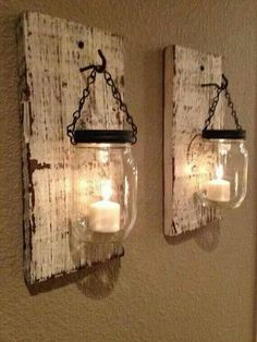 These as centerpieces mason jars with dark top single candle but sitting on a piece of distressed square shape wood simple elegant and rustic