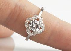 Elegant vintage halo diamond engagement ring with central round brilliant cut diamond and scalloped border and grain set diamond halo surround above plain shoulders. Elegant!