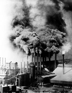"""Smoke pouring into the air from a Pittsburgh steel mill, 1906. Each month the steam boilers and furnaces of its industries, railroads, and homes dumped 100 tons of pollutants on its streets."" Steel was the main component in the Model-T. One of the largest industries for steel was the automotive industry. Once a middle class friendly automobile was made, more and more vehicles were being designed using more resources and polluting the air further."
