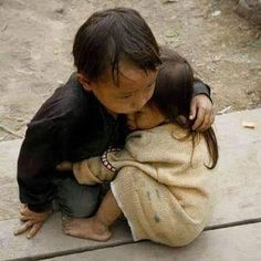 2 year old sister being protected by her 4 year old brother in Nepal. Amazing photo.