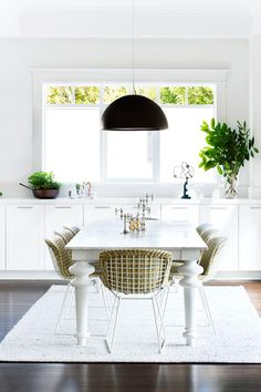 """**Room #25 by Sally Richardson Interior Architecture** A turned-leg dining table with marble top is centred against a beautifully framed picture window in this white-on-white Melbourne room. """"The Bertoia chairs are upholstered in a subtle patterned fabric that pays tribute to the 1950s, the era in which the chairs were designed, while still remaining contemporary,"""" says Sally. The Flos Skygarden pendant light is a graphic punctuation point. Photo: Martina Gemmola  [VOTE FOR THIS…"""