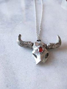 Hand carved and casted in sterling silver ox head.   Similar to our Ox head choker, this ox head is hand carved and casted with red man made pear shape cubic ziconia.   Sterling Silver link chain.