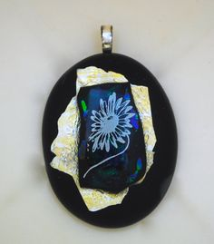 In this wearable art piece, I made layers of opal glass, transparent glass and dichroic green and purple glass and fused silver leaf in between. I then topped it off with a white flower decal fired permanently into the beautiful glass! It is one-of-a-kind, signed by me, the