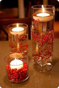 Submerge colorful elements in water-filled hurricane vases and float candles on top. Some great ideas would be branches, fruits, fir or herb sprigs, flowers, colored marbles....so many things.