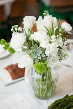 succulents tulips and ranunculus white wedding centerpiece / http://www.himisspuff.com/white-tulip-wedding-ideas-for-spring-weddings/4/