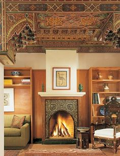Moroccan artisans created the library's traditional carved and painted ceiling as well as the tiled fireplace, over which hangs a Moroccan calligraphy work. Above the sofa, with an Osborne & Little stripe, is a print by Robert Kelly. The chair and table are Syrian.