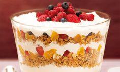 Taça com iogurte, granola e frutas secas.