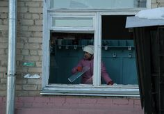 In this photo provided by Chelyabinsk.ru a woman cleans away glass debris from a window after a meteorite explosion over Chelyabinsk region on Friday, Feb. 15, 2013. A meteor exploded in the sky above Russia on Friday, causing a shockwave that blew out windows injuring hundreds of people and sending fragments falling to the ground in the Ural Mountains. The Russian Academy of Sciences said in a statement hours after the Friday morning fall that the meteor entered the Earth's atmosphere.