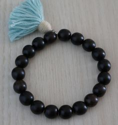 Natural Ebony Wood Bead Bracelet/Natural Wood Bead Bracelet/Boho Chic Bracelet  This Zen and Bohol chic stretch bracelet is made of large natural Ebony wood beads, I added a cotton tassel meditation to bring the bracelet a unique design, this bracelet is mounted on elastic cord.  This bracelet is perfect for meditation and relaxation, also you can wear it every day.   Product details: Measurements:  Length: fit 7 wrist (this can be adjustable upon request)  *10mm Natural Ebony wood ...