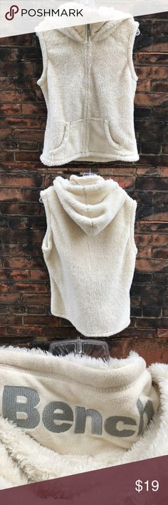 """Bench Soft Vest w/Hood size L Super soft as a kitty! Pre-loved and in good shape. All poly material. Shoulder to hem: 23"""", pit to pit: 22"""". Size L. A light cream color.  Shop smart by maximizing your shipping $. Use the filter function and peruse my closet of over 1,000 items! Bundle and save!! Bench Jackets & Coats Vests"""
