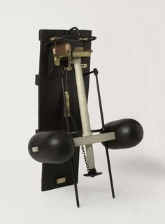 Thomas Cook | Reddingsboei, Thomas Cook, 1819 | Reddingstoestel tegen een schuine wand. Het toestel bestaat uit een stel drijvers verbonden door een dwarsbalk met een verticale ronde paal in het midden. Het wordt tegen de wand gehouden met twee geleidestangen door de dwarsbalk en is geborgd met een ketting; de ketting wordt met een sliphaak losgemaakt, die met een touw door de wand wordt bediend, waarna het toestel langs de geleidestangen naar beneden valt en vrij komt. Bovenop de paal is…