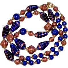 Vintage Italian Venetian Murano Art Glass Bead Necklace features uniquely shaped cobalt blue oblong beads with swirly bands of gold fluss or aventurine. The large beads are separated by sparkling round aventurine gold fluss beads and deep blue glass beads, all of which are bordered by lacy filigree caps.