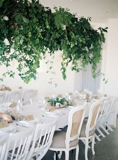 Elegantly rustic tablescape with a suspended centerpiece consisting of assorted foliage | Photo by Byron Loves Fawn