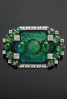 An Art Deco emerald, platinum and diamond brooch, by Cartier, circa 1925, modified by Cartier in 1927. Platinum, set with emeralds, diamonds and enamel. #Cartier #ArtDeco #brooch