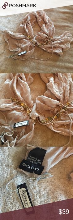 NWT. Bebe 100% silk scarf. NWT. 100% silk. Tan color. Beautiful details at both end. Decorative bead strings and two tail strings on each end for easy knot. No need to wrap scarf in a knot. Simply use the strings. bebe Accessories Scarves & Wraps